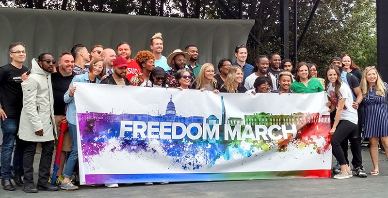 "A couple dozen speakers and singers gather on stage behind a rainbow-colored ""Freedom March"" banner."