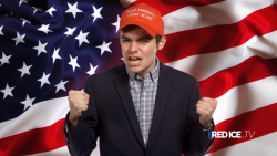 Nick Fuentes stands in front of American flag with a Trump campaign hat on